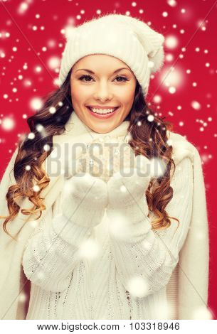 winter, people, happiness concept - happy woman in hat, scarf and mittens with christmas ball
