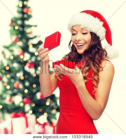 christmas, x-mas, winter, happiness concept - smiling woman in santa helper hat with gift box