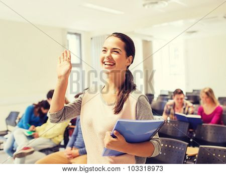 education, high school, gesture, teamwork and people concept - group of smiling students with notepads waving hand in lecture hall