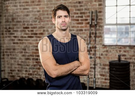 Serious man with arms crossed at gym