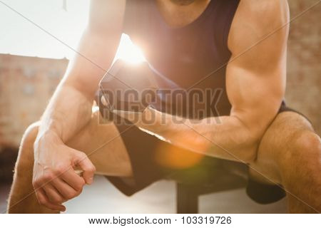 Midsection of man lifting dumbbell at the gym