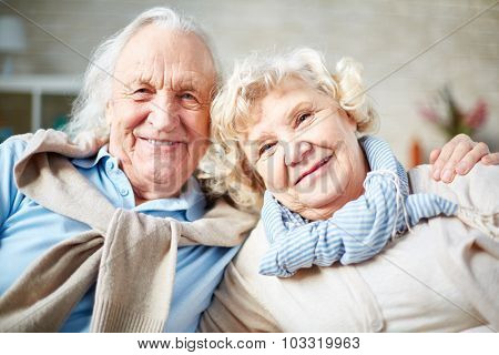 Affectionate elderly couple looking at camera with smiles
