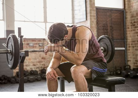 Tired man sitting on the bench at the gym