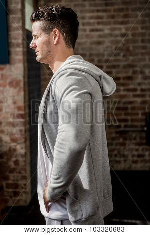 Side view of man wearing hood at gym