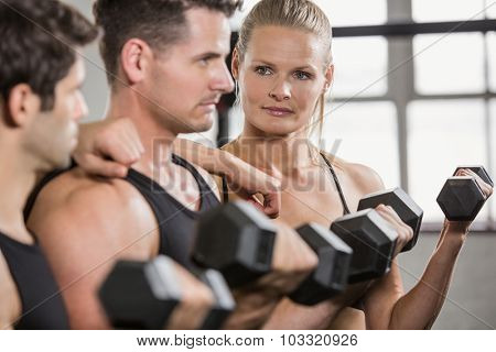 Focused people lifting dumbbell at the gym