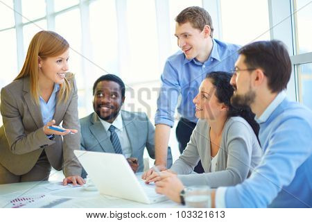 Pretty manager explaining her viewpoint upon project to co-workers