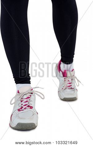 Low section of woman wearing sports shoes against white background