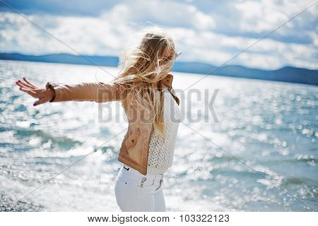 Happy long-haired girl standing with outstretched arms by the seaside