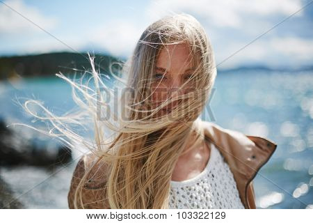 Blond girl with long hair looking at camera by the seaside