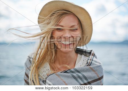 Blond girl in hat looking at camera outdoors