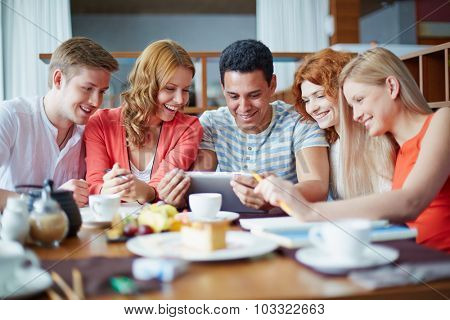 Modern teens with touchpad networking in cafe