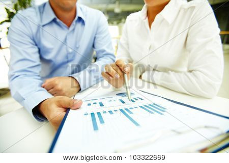 Businesswoman with pen explaining data to colleague