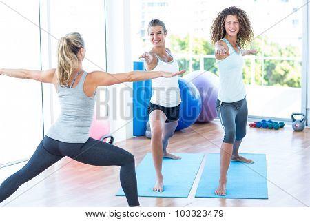 Women doing warrior II pose in fitness studio