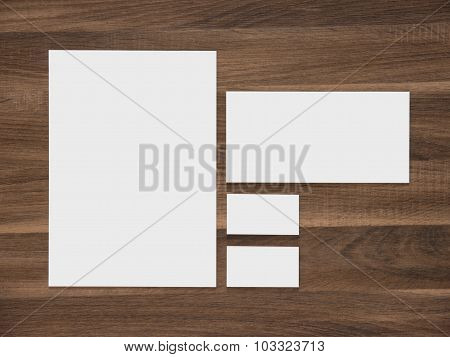 Blank paper, envelope and business cards on wooden background.