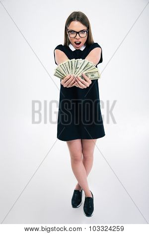 Full length portrait of a cheerful female student holding dollar bills isolated on a white background