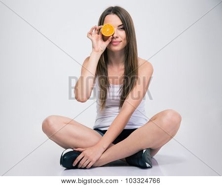 Portrait of a smiling girl sitting on the floor and covering one eye with orange isolated on a white background