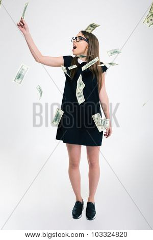 Full length portrait of a young cute standing under rain with dollar bills isolated on a white background