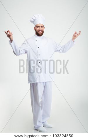 Full length portrait of a smiling chef cook showing welcome gesture isolated on a white background