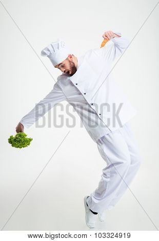 Full length portrait of a funny chef cook holding vegetables and dancing isolated on a white background