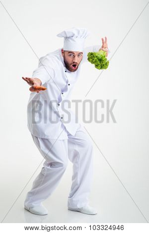 Full length portrait of a funny chef cook dancing isolated on a white background