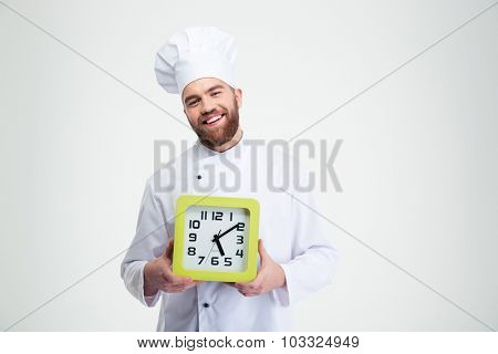 Portrait of a laughing male chef cook holding wall clock isolated on a white background