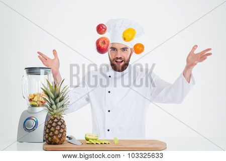 Portrait of a hapy male chef cook juggle with fruits isolated on a white background