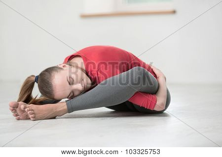 Portrait of a happy flexible woman doing yoga exercises in gym
