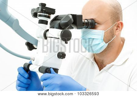 Dentist using dental microscope during inspection