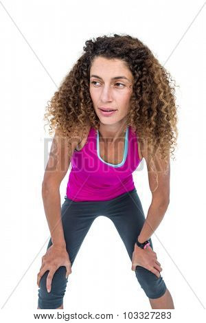 Tired young woman with hand on knees against white background