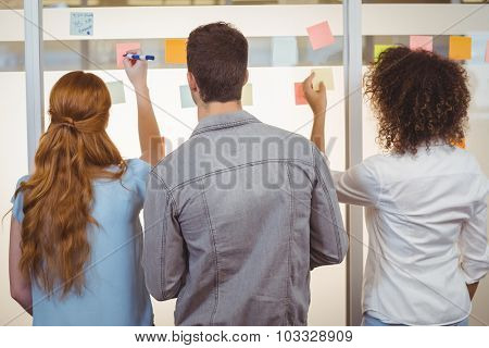 Rear view of business people writing on adhesive notes on glass wall during meeeting in office