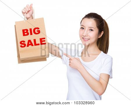 Woman finger point to shopping bag and showing phrase of big sale