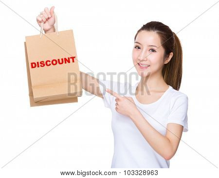 Woman finger point to shopping bag and showing a word of discount