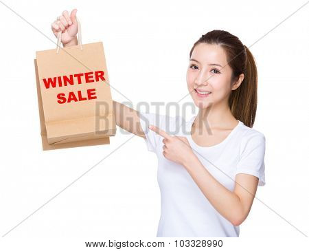 Woman finger point to shopping bag and showing phrase of winter sale