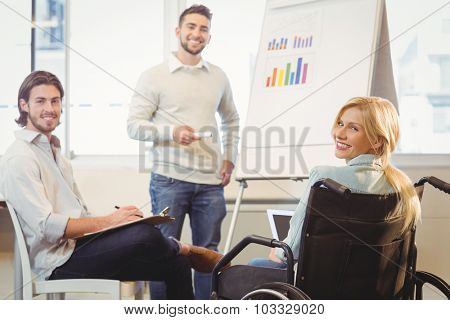 Portrait of confident business people with whiteboard during meeting in creative office