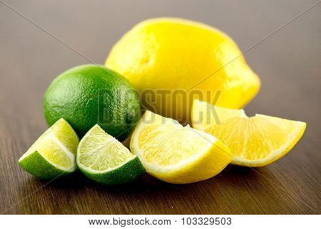 Macro Closeup Of Lime And Lemon Wedges With Whole Fruits Behind Them