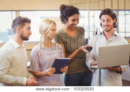Business team standing together and using laptop in creative office