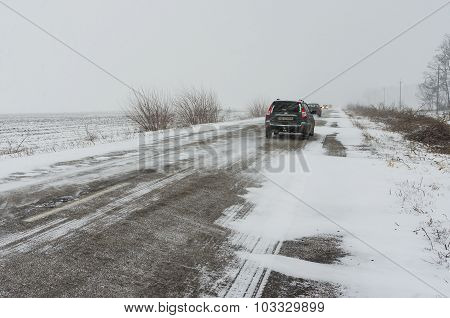 Private transport on a snowy highway struggle forward through snow-drift