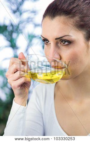 Woman looking away while drinking herbal tea