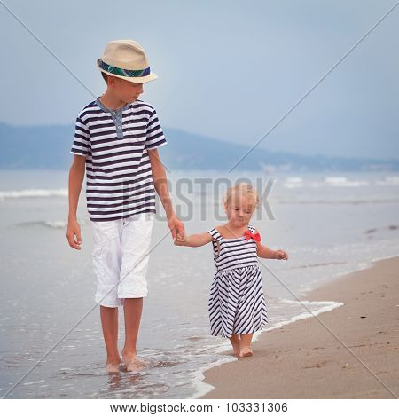 Happy Older Brother And Younger Cute Sister Walking On Sea Coast