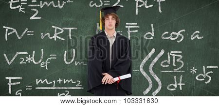 Student in graduate robe against green chalkboard
