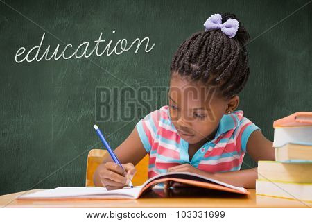 The word education and cute pupils writing at desk in classroom against green chalkboard