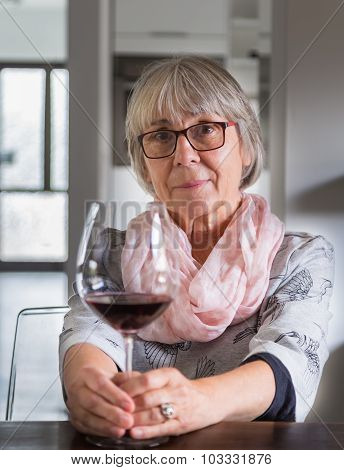 Senior Woman Drinking Wine At A Table