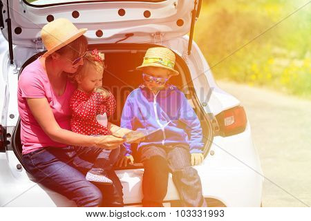 family looking at map while travel by car