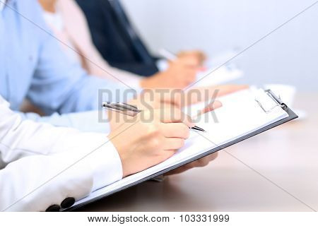Image Of Business Partners Discussing Documents And Ideas At Meeting
