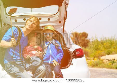 family taking selfie while travel by car