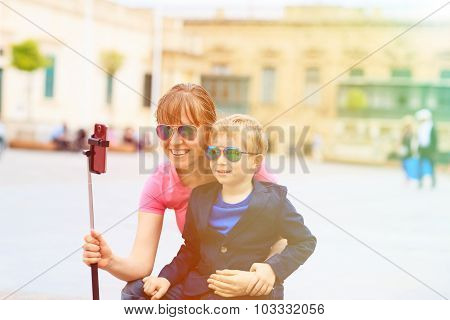 mother and son taking selfie stick picture while travel in Europe