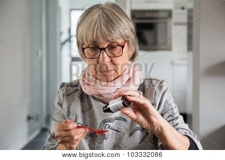 Senior Woman Drip Medication On Spoon