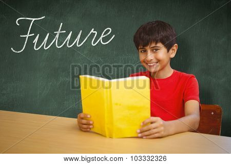 The word future and portrait of boy reading book in library against green chalkboard