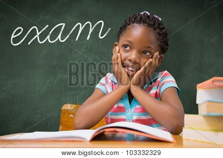 The word exam and pupil sitting at her desk against green chalkboard