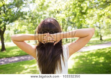 Rear view of woman with hands behind head while standing in park